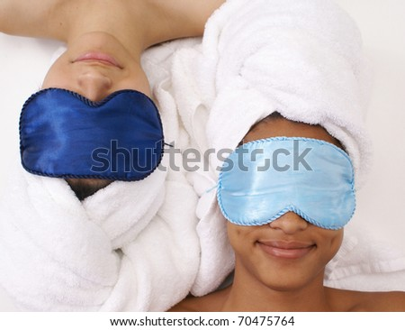 Two young females relax at the spa with turbans and satin eye masks.