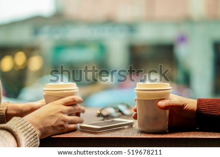 Two young friends drinking coffee in paper take away cup - People having a break sitting in bar restaurant toasting cappuccino - Winter concept - Focus on man hand - Soft saturated retro filter #519678211
