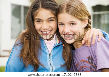 Two young friends embracing and smiling