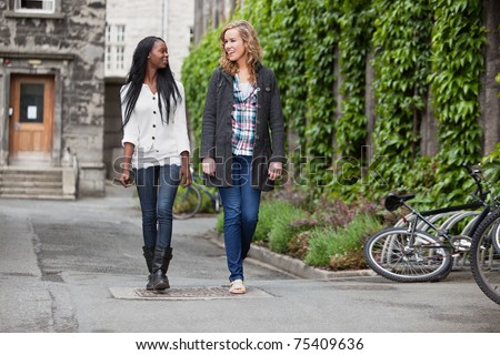 Two young friends having a casual chat while walking on street