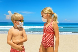 Two young funny children wearing sunglasses, protective mask on sea beach. Summer tours, cruises cancellation due to coronavirus COVID-19 world epidemic. Safe travel destinations for family vacation