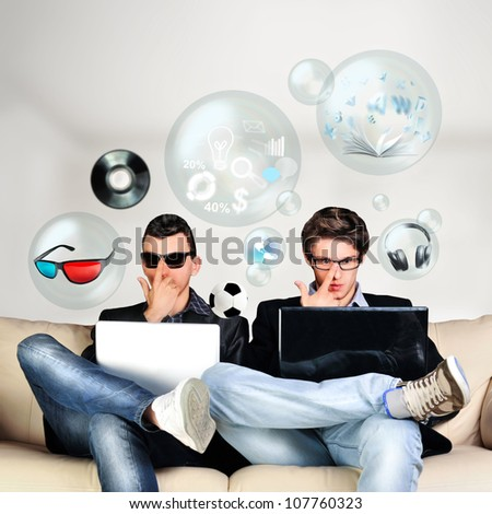 Two young gamers sitting together on sofa and using their laptops. Different objects are flying around them from laptop screen