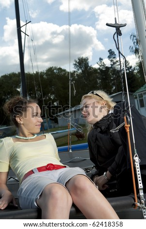 two young girl discussing with each other resting on yacht board and having positive facial expression. shot with studio strobe on location.