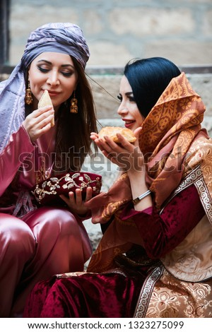 Two young girl friends dressed in traditional Azerbaijani clothes. Beautiful girl friends having fun with Azerbaijan national pastry baklava and shekerbura. Novruz holiday celebration concept