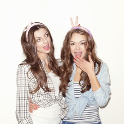 Two young girl friends having fun. One showing sign, other laughing. Wearing casual clothes and headband. Inside