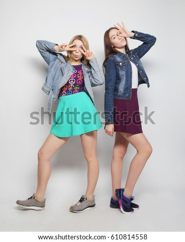 Two young girl friends having fun together. Hugging each other and smiling. Hipster style.