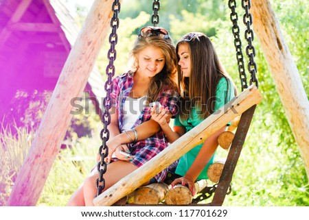 Two young girl friends sitting on swings in park outdoors and looking on mobile phone on the bright day of summer background