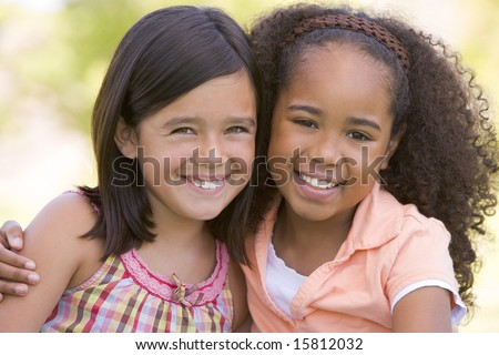 Two young girl friends sitting outdoors smiling - stock photo