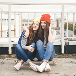 Two young girl friends sitting together on long-board and having fun. Outdoors, lifestyle.