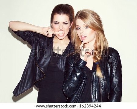 Two young girl friends standing together and having fun. Looking at camera. Inside