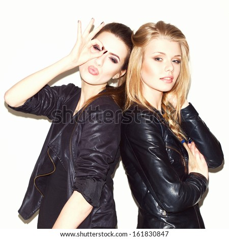 Two young girl friends standing together. Brunete having fun and showing sign with her hand. Looking at camera. Inside