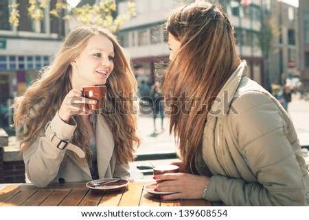 Two young girl-friends talking and drinking coffee in cafe, outdoors