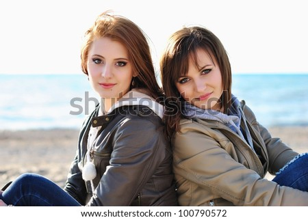 Two young girl friends together at the beach