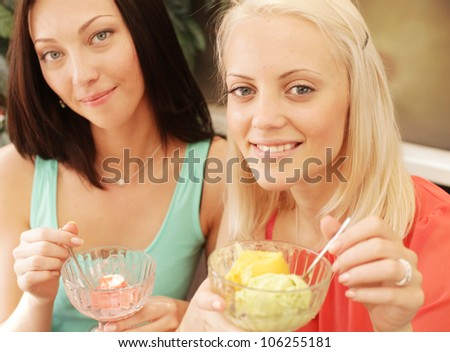 Two young girl having coffee break and eating ice cream