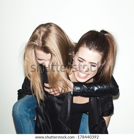 Two young girl hipster friends standing together having fun indoor
