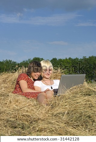 Two Young girl work with laptop in a stack of hay