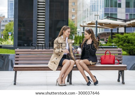 Two young girlfriends sitting on a bench in the town center