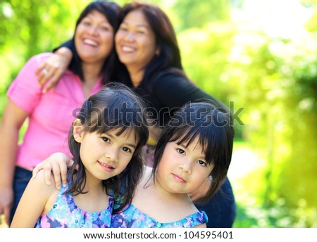 two young girls and two chinese women hugging in the park. Concept of sister's love.