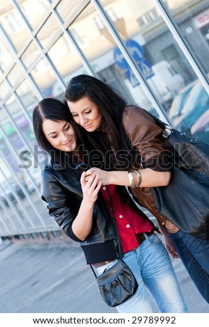 Two young girls are looking on mobile phone.