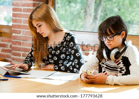 Two young girls concentrating on digital devices at desk.
