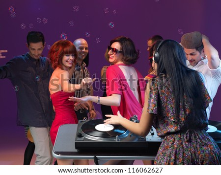 two young girls dancing and enjoying the party, with othe people dancing in the background and with dj mixing music