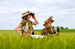 Two young girls dress up as explorers.They pose  in the outdoors observing the countryside. They are dressed with jungle hats and khaki safari clothes.