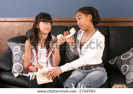 Two young girls experiment with telecommunications at a birthday party