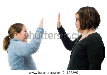 Two young girls giving each other a high five with their hands, isolated against a white background