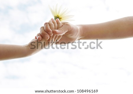 Two young girls' hands being held against the sky while holding a flower.