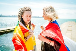 Two young girls hold on their shoulders a rainbow flag and a Russian flag stand on a pier against the sea. High quality photo