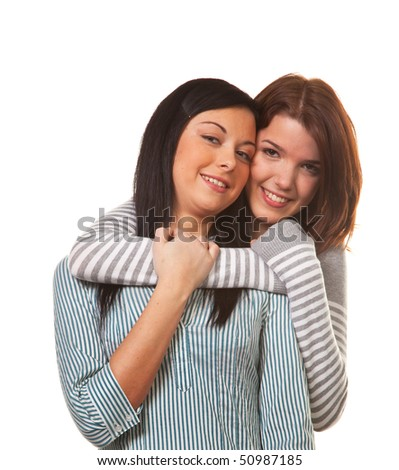 Two young girls hug each other happily and get along