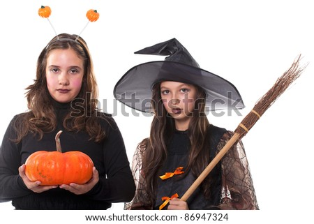 two young girls in halloween costumes holding a broom and a pumpkin