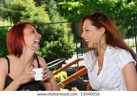 two young girls in open-air cafe
