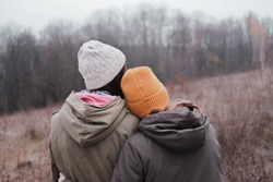 Two young girls in parka coats and knitted hats hug each other on autumn forest background. Concept of togetherness and support, woman friendship, homosexual relationship