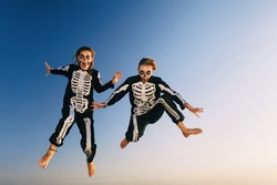 Two young girls in scary skeleton costumes jump high in air with fun before Halloween night party on sunset sea beach. Active people, lifestyles and funny event celebrations on holidays