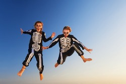 Two young girls in scary skeleton costumes jumping with fun high in air before Halloween night party on sunset sea beach. Active people, lifestyles and event celebrations on tropical holidays.