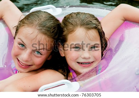 Two young girls in swimming pool with float, colors in lavender and purple