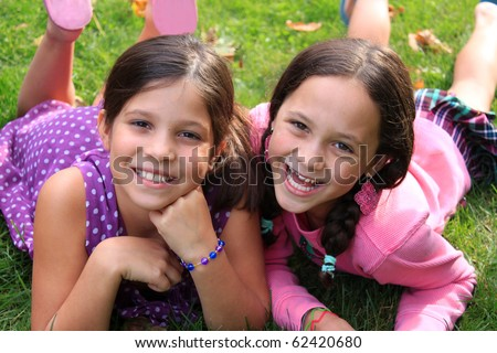 Two young girls in the ages of ten and eight that could be sisters or best friends laying on the grass and smiling whitle wearing colorful clothing