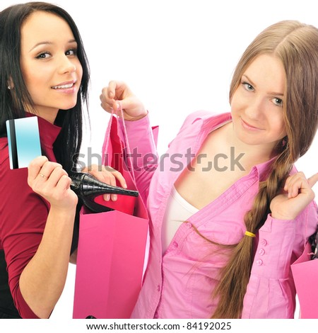Two young girls laughing and holding their new purchases. Shopping concept