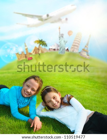 Two young girls laying on a grass against world's famous buildings. Educational traveling concept
