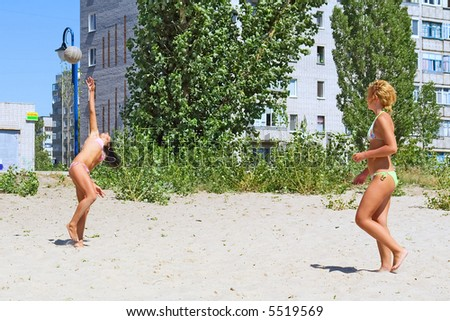 Two young girls play beach volleyball. Shot in July, near Dnieper river, Ukraine.