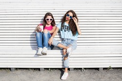 Two young girls. Portrait of two pretty hipster sitting on a bench, resting in the sun. Girls smile, have fun. Outdoor lifestyle portrait. Girl with glasses drinking coffee.