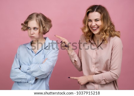 Two young girls pose for a Studio portrait on isolated background. One of them laughs and has fun mocking the failure of the other. The concept of trolling to be bullying and friendships