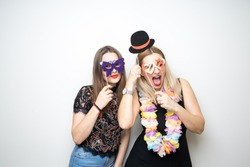 two young girls pose photo booth props happy funny white background smile models