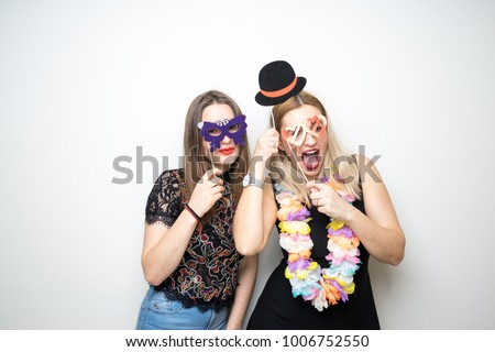 two young girls pose photo booth props happy funny white background smile models  #1006752550