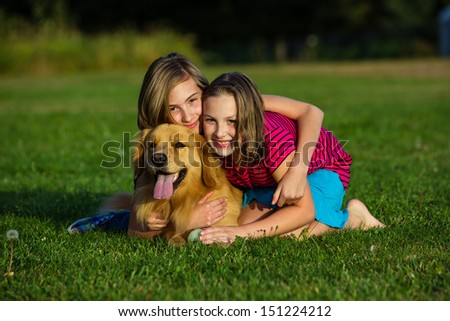 two young girls pose with a beautiful golden retriever dog