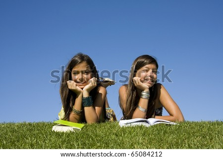 Two young girls reading books at the park