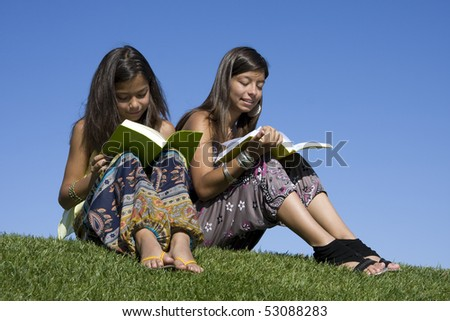 Two young girls reading books on the park
