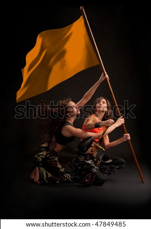 Two young girls rising flag with paintball gun in their hands. File includes clipping path of flag.