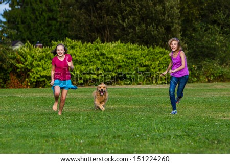 Two young girls running fast with a golden retriever dog